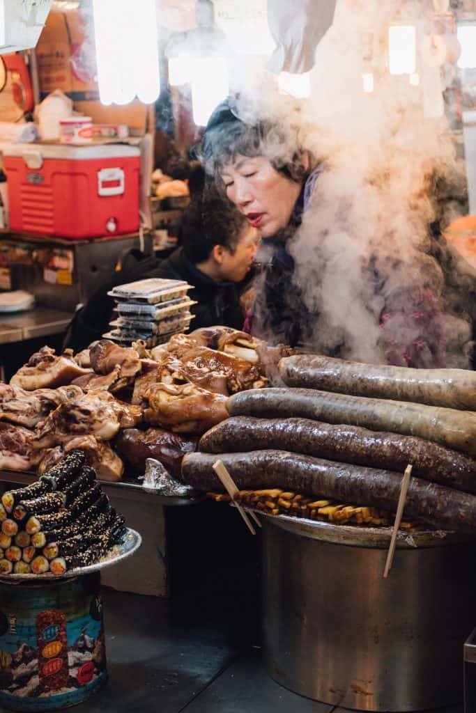 على يمين الصورة سونداي - نقانق الدم، وعلى يسارها كيمباب ( لفافات الأرز) امرأة تقدم الطعام في كشك طعام في كوريا